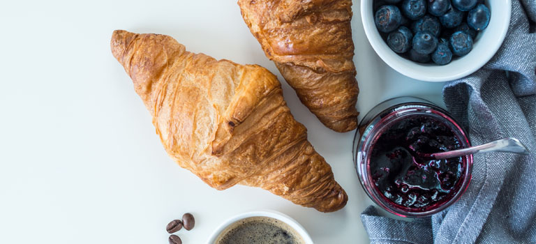 Französisches Butter-Croissant serviert mit frischen Blaubeeren und fruchtigem Gelee